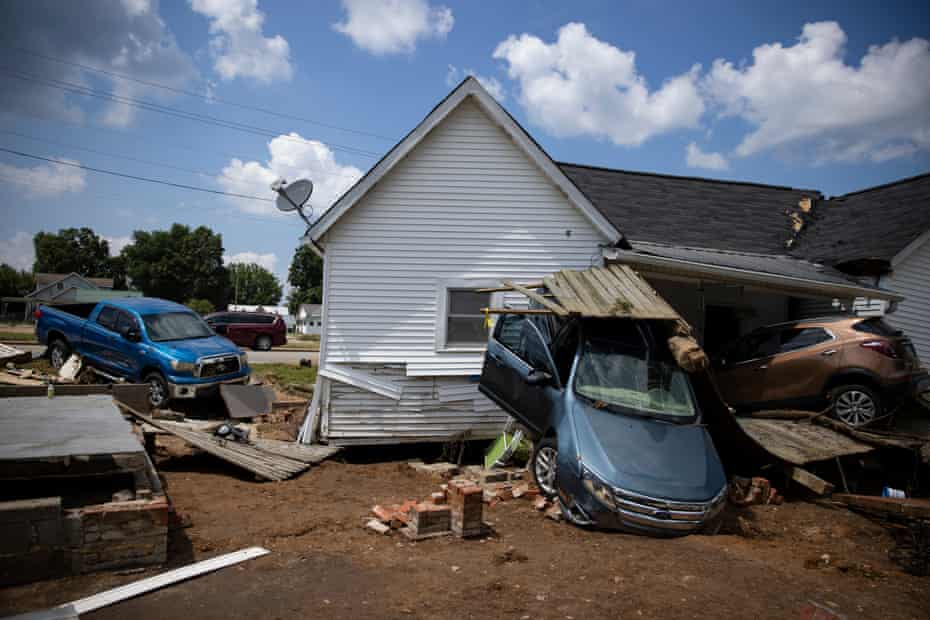 Vehicles are piled up next to a house destroyed by flooding on Monday in Waverly, Tennessee.