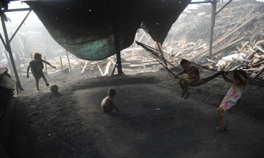 Children playing football on an open stove used for smelting woods into charcoal at an unregulated charcoal factory locally known as 'Ulingan' in the slums of Manila, Philippines.