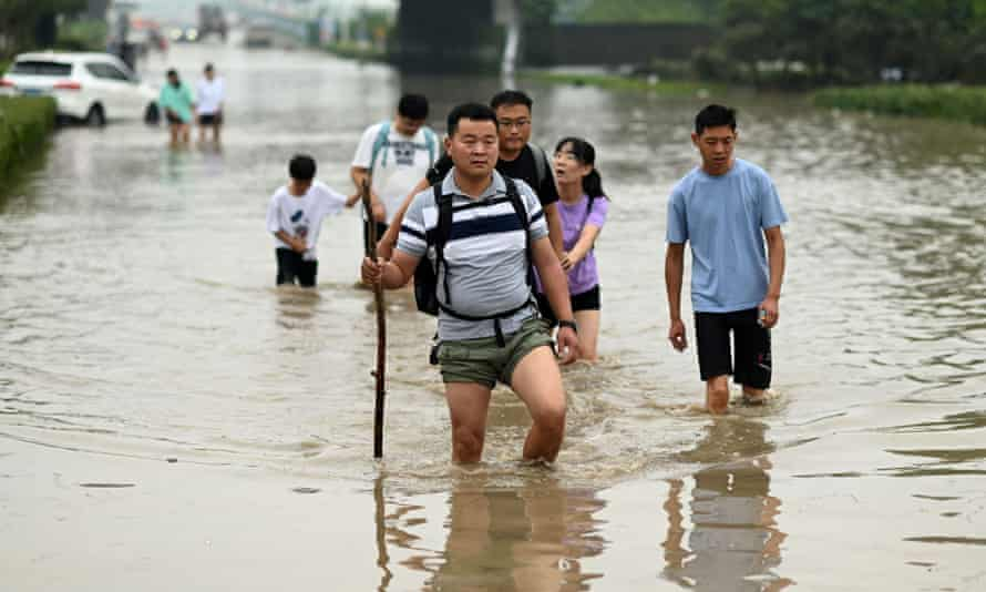 People cross a flooded street in Zhengzhou, China, 23 July