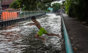 Kids play in a polluted canal in central Bangkok.