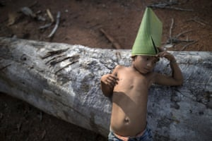 A Tembe child leans on a log as he holds on to a make-believe hat he constructed from a giant leaf, in the Ka 'a kyr village.