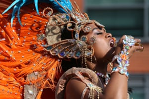 A dancer sips a drink at the start of the parade on the second and final day of the Notting Hill carnival, London, UK