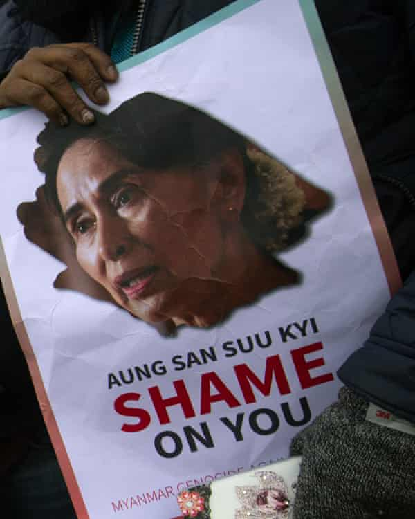 Demonstrators hold signs outside the international court of justice where Aung San Suu Kyi was attending the first of three days of hearings in The Hague.