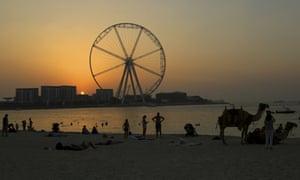 The sun sets behind the Ain Dubai.
