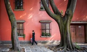 Man walks past red-painted houses on Avenida Francisco Sosa, Coyoacán, Mexico City, Mexico.