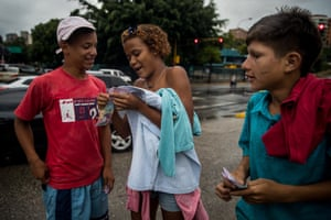Paola (centre) counts money collected from other children at a traffic light in Caracas