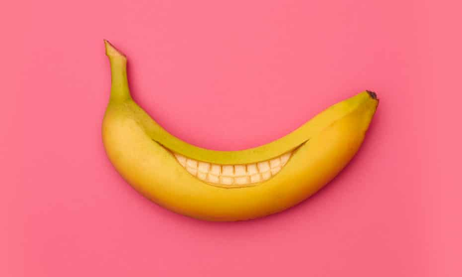 A banana cut into a smile inside its skin, against a pink background