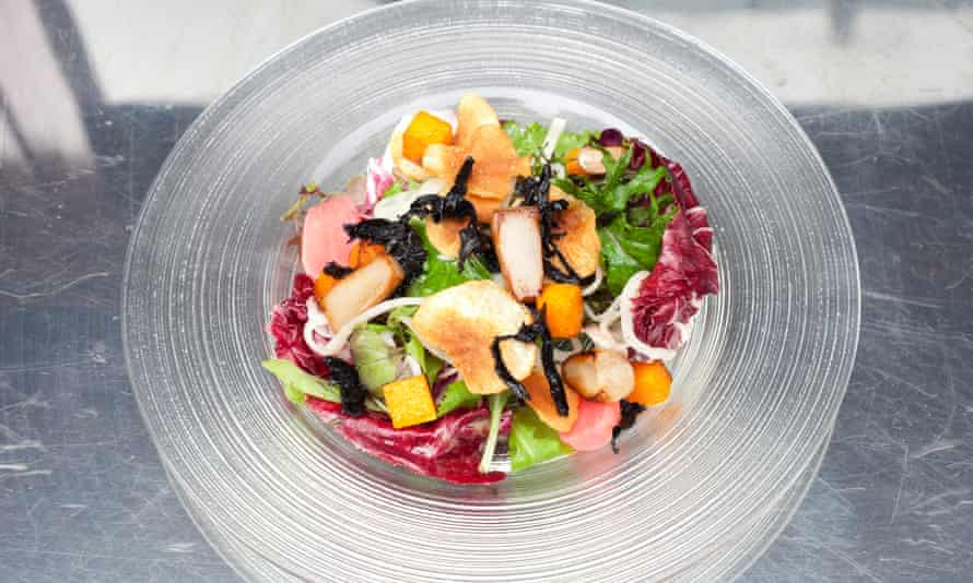 The brightly coloured autumn salad on a glass plate.