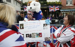 Royal fans gather with placards, flags and balloons as they wait for in Windsor