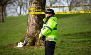 A police officer stands by tributes in Queen's Park, Bolton.