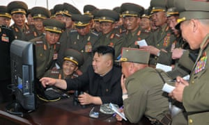 The North Korean leader, Kim Jong-un, looks at a computer along with military personnel