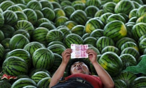 A watermelon vendor examines yuan notes in Changzhi, Shanxi province. Goldman Sachs and Morgan Stanley think the currency will fall in value this year.