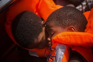 Two young migrants sleep after being rescued in the Mediterranean north of Sabratha, Libya.