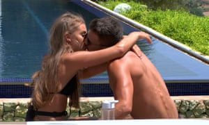 Two people kissing by a pool