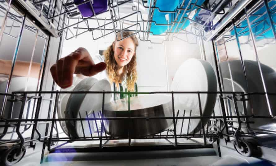 Seen from inside dishwasher, a young woman unloads dishes.