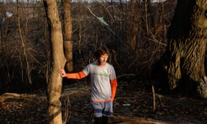 Lawrence Warriner leans against a tree in the forest