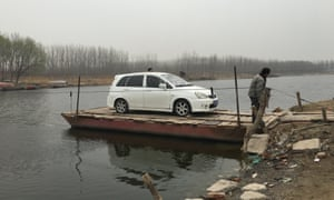A ferry transports a sole car across the river in Hebei province, China.