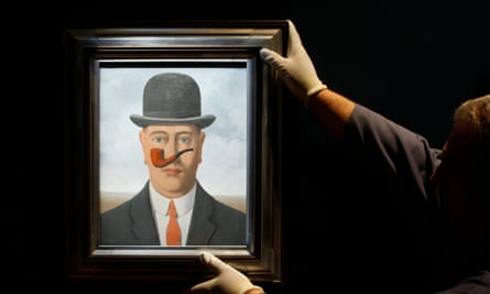 A worker adjusts a painting by Belgian artist Magritte in Brussels