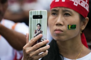 Yangon, Myanmar. A woman holding a mobile phone with an image of Aung San Suu Kyi, Myanmar's state counsellor, takes a video during a protest in support of amendments to the 2008 Myanmar constitution