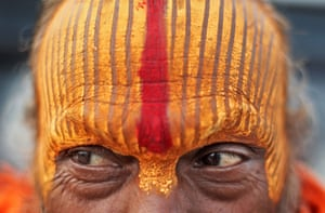 Prayagraj, India. A Hindu holy man known as a Sadhu stands on the banks of the Ganges before taking a dip during Kumbh Mela