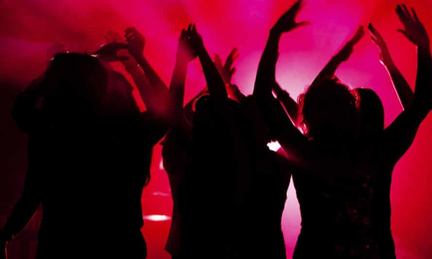 Silhouette of people dancing in club with lightshow