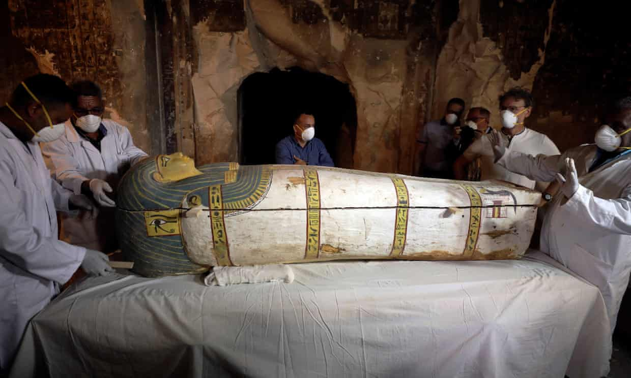Archaeologists remove the cover of a ancient Egyptian sarcophagus in Luxor.