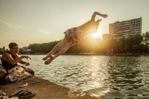 A swimmer, at sunset, dives into the Canal de l'Ourcq in east Paris watched by a friend. We usually swim in the Canal de l'Ourcq in east Paris. When it's hot we like having a picnic, drinking rosé close on the canalside and having a plunge between glasses. We call this 'apéro-splash'.