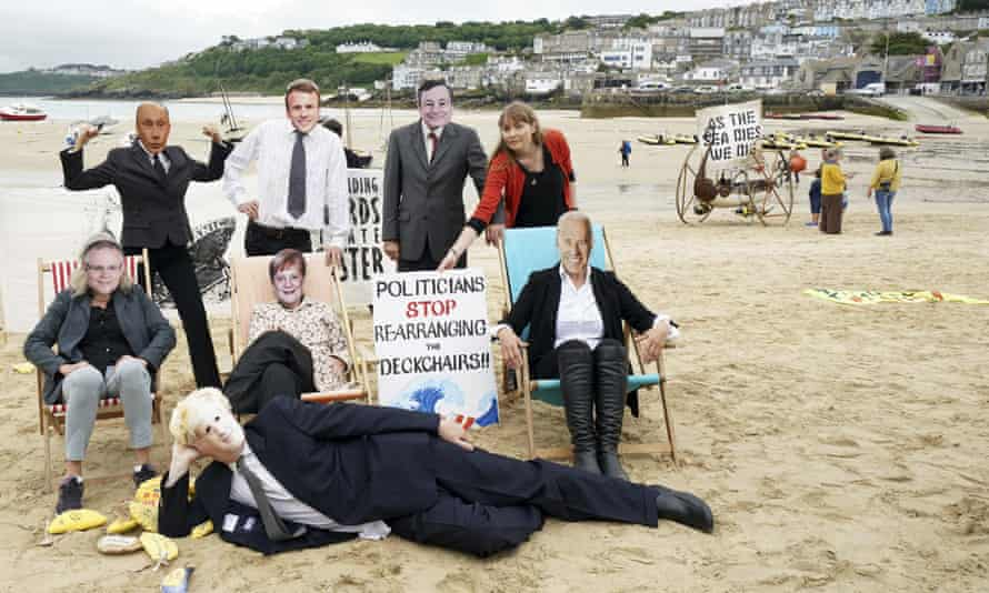 Activists pose with faces of the G7 and other world leaders, including Scott Morrison, as they demonstrate on the beach near the meeting in St Ives, Cornwall.
