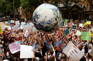 An inflatable planet Earth is bounced around the crowd during a climate change awareness rally at Sydney town hall in Australia