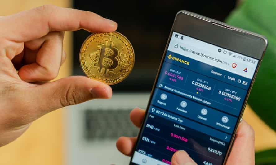 a bitcoin coin and Binance app on a smartphone