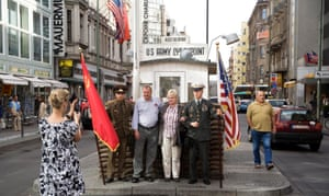 Tourists pose at the replica hut on the site of Checkpoint Charlie, Berlin