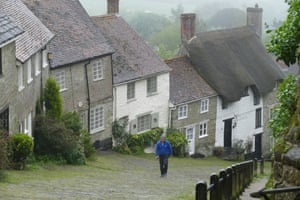 Dorset, UK No more summer here: a man walks up Gold Hill in Shaftesbury in the heavy rain