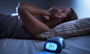 Sleepless woman with alarm clock on the bed