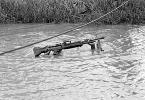 A six-foot-five machine gunner with the U.S. 9th Infantry Division is submerged except for his rifle as he crosses a muddy stream in the Mekong Delta south of Saigon, September 10, 1968
