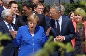Angela Merkel gestures to the Nato secretary general, Jens Stoltenberg