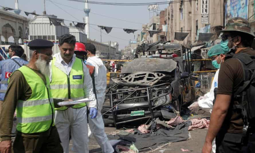 Security officials and a bomb disposal team survey the site after a blast in Lahore.