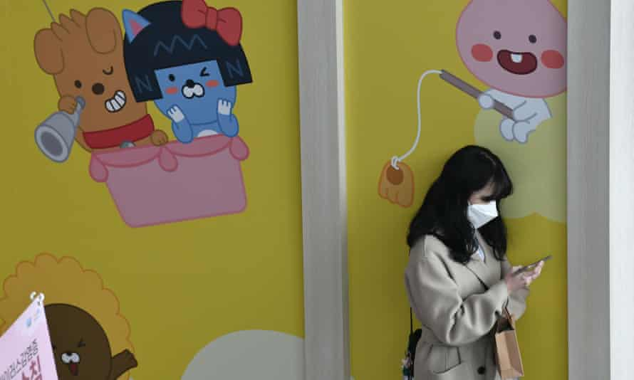 A woman wearing a face mask uses her phone in a railway station in Seoul