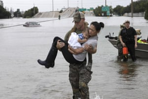 Houston Police SWAT officer Daryl Hudeck carries Catherine Pham and her 13-month-old son Aiden after rescuing them from their home, which was surrounded by floodwaters