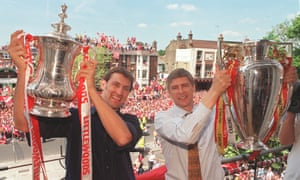 Arsène Wenger and Tony Adams hold the FA Cup and Premier League trophies after Arsenal won the double in 1998