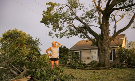 A woman stands in her front yard in Cedar Rapids, Iowa, after the storm, which blew over trees, flipped vehicle, and left thousands without power.
