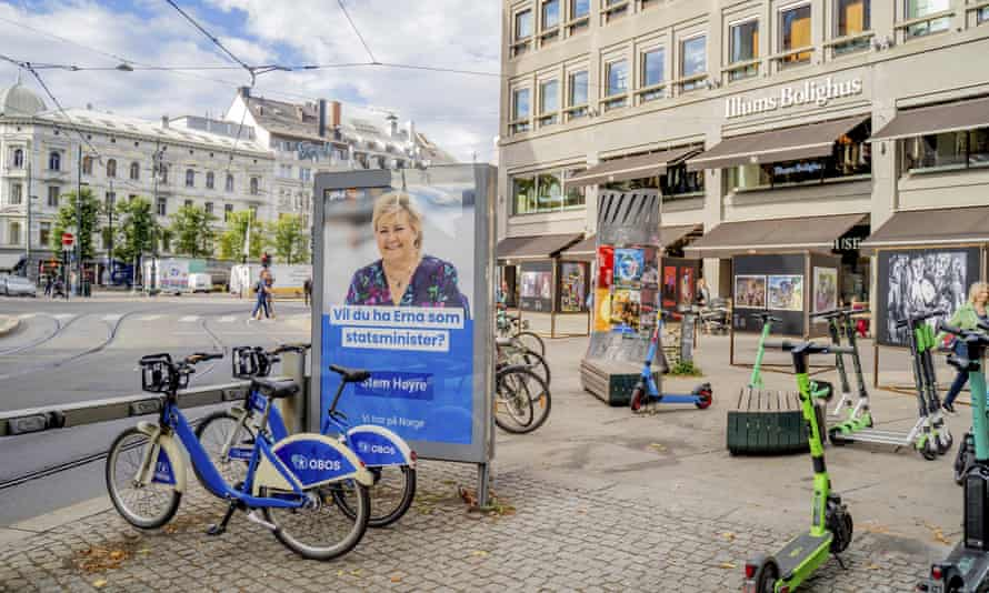 An election poster on an Oslo street is surrounded by bicycles and shows Norway's prime minister, Erna Solberg.