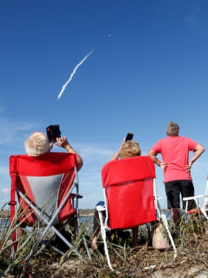Spectators at Cocoa Beach near Cape Canaveral watch the rocket launch.