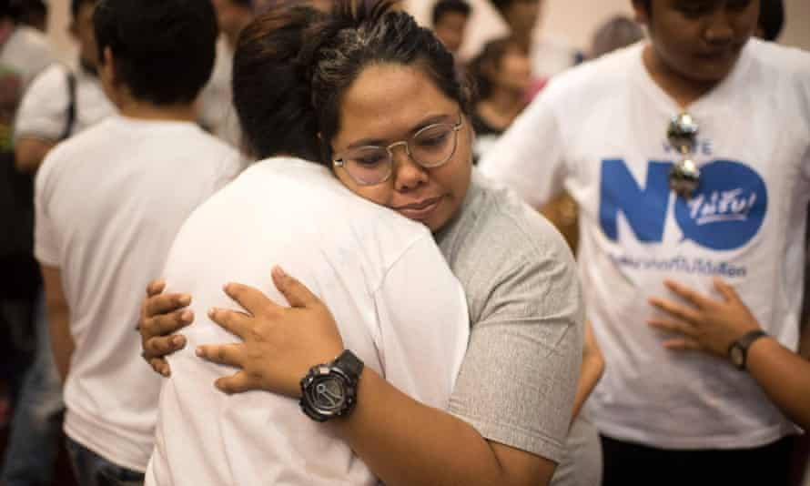 Members of the New Democracy movement, an anti-junta activist group, hug after learning of the yes vote