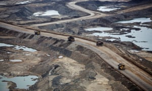 Trucks carry raw tar sands near Fort McMurray, Canada.