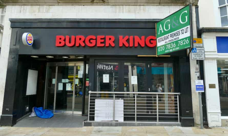 A person sleeping rough in the doorway of a shuttered Burger King outlet in Oxford