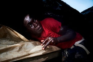 A sand digger takes shelter under a plastic tarpaulin during a storm over the Niger River