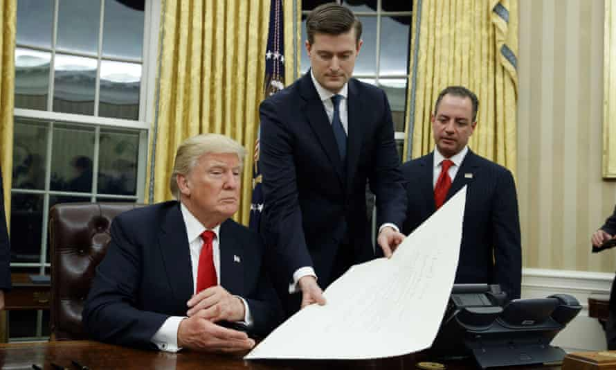The then White House staff secretary, Rob Porter, center, hands Donald Trump a document in the Oval Office in January 2017, as the then chief of staff Reince Priebus, right, watches.