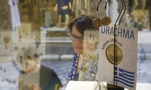 Tourists look at a display of jewellery made from old drachma coins in Athens. The government is still insisting that a return to the old currency is not being contemplated.