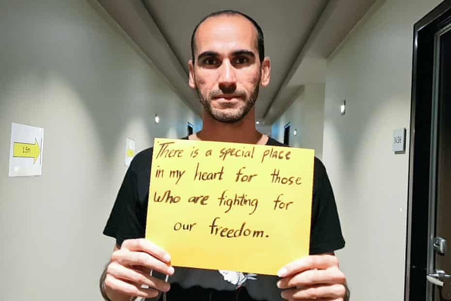 Moz Azimi holds a sign