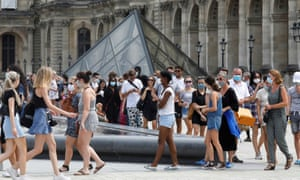 Visitors wearing protective face masks queue to enter the Louvre Pyramid in Paris, as France reinforces mask-wearing as part of efforts to curb a resurgence of the coronavirus.